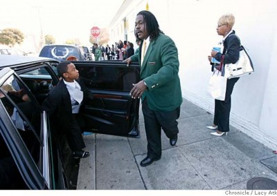 Anthony London greets 9 year old Laval Dunbar as he and his family arrive to the church, for his brother