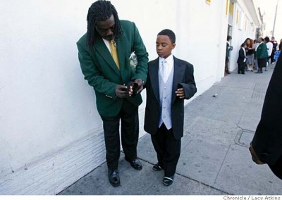 Anthony London rolls up the sleeves of 9 year old Laval Dunbar before he goes into the Good Hope Church for his brother Wayne Gordon Jr's funeral
